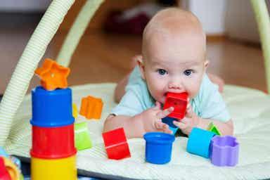 En baby med et leketøy i munnen