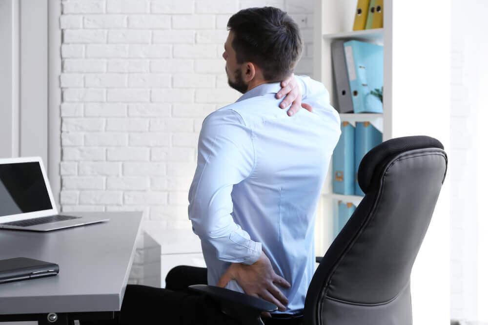 Mann som lider av smerter i skulderbladet