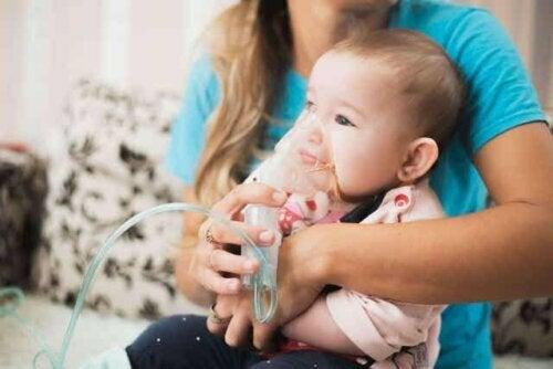 En baby iført en oksygenmaske.