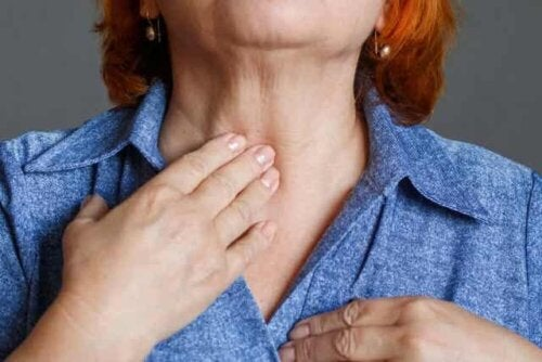 En eldre kvinne som holder seg på halsen.