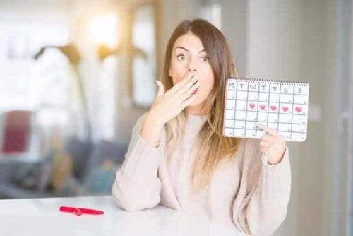 En kvinne som holder opp en kalender over menstruasjonssyklusen.