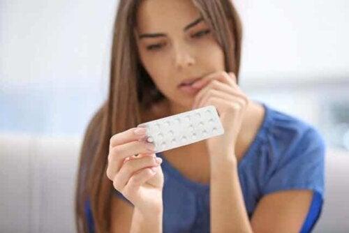 En kvinne som ser på p-piller.