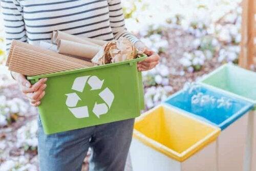En kvinne som sorterer resirkulerbart materiale.