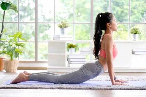 En kvinne som utfører yoga i hjemmet sitt.