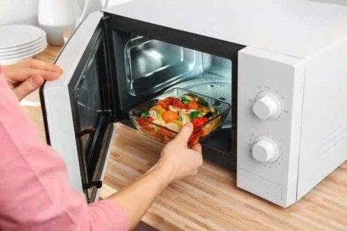 En kvinne som varmer opp mat i mikrobølgeovnen ved hjelp av et glassfat.