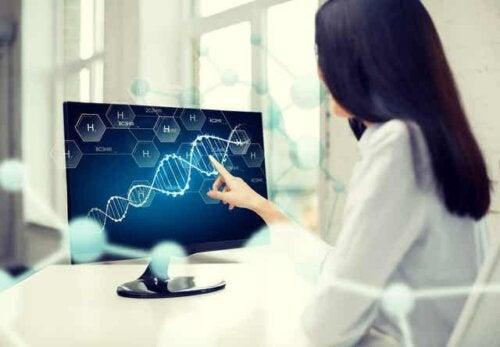 En lege som ser på en streng DNA på en dataskjerm.