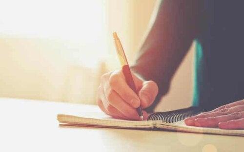 En person som skriver i en notatbok.
