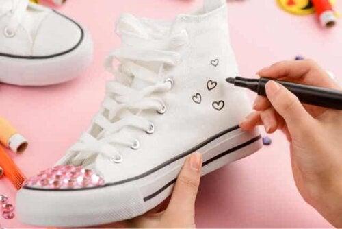 En person som tilpasser Converse-skoene sine.