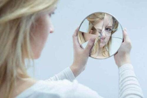 En ungdomsjente som ser på seg selv i et ødelagt speil.