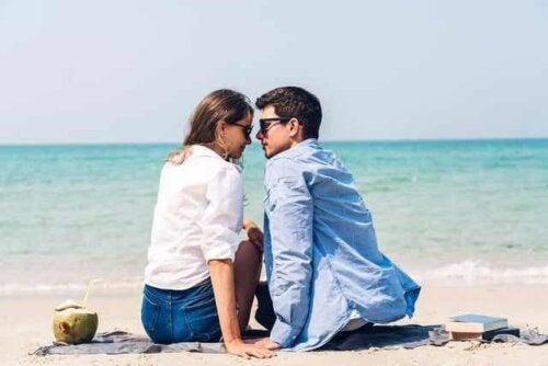 Et par som sitter på stranden og ser inn i hverandres øyne.