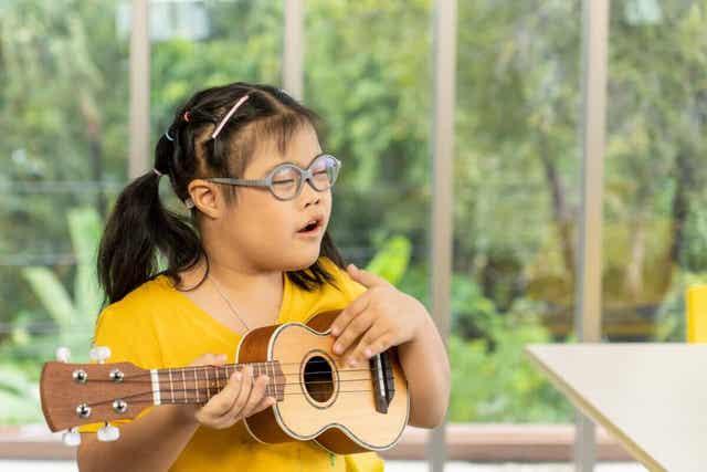 Et barn med Downs syndrom som spiller ukulele