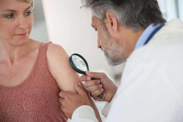 En hudlege som inspiserer pasientens hud.