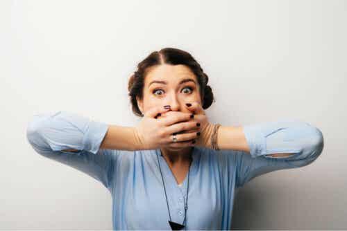 Kvinne som holder hendene for munnen.