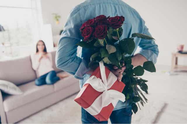 En mann som overrasker partneren med blomster og en gave