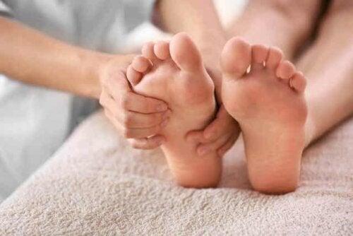 En fotterapaut som masserer en pasients fot.