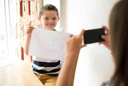 En gutt med downs syndrom som holder en tegning mens moren tar et bilde.