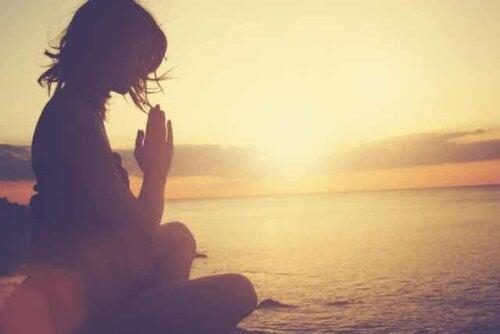 En kvinne som mediterer på stranden ved solnedgang.