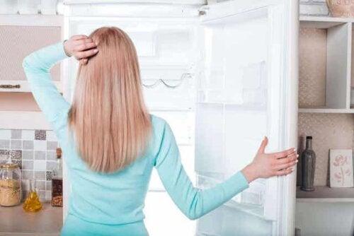 En kvinne som ser på fryseren sin.