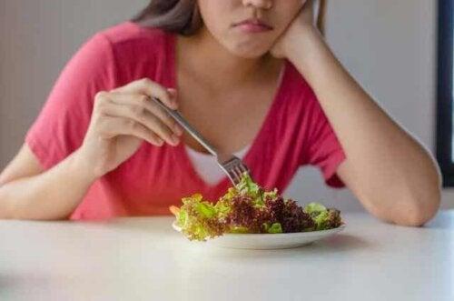 En kvinne som spiser en salat.