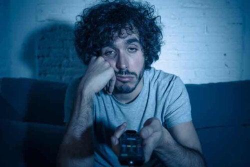En mann som kjeder seg mens han ser på TV i mørket.