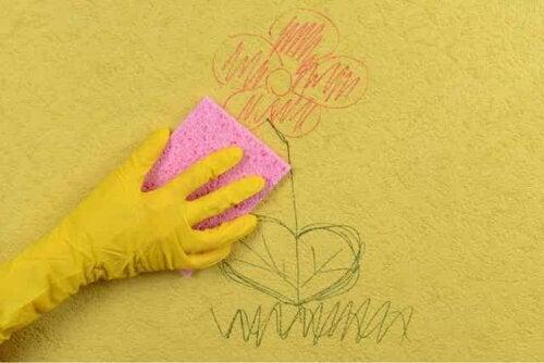 En person som bruker en svamp til å rengjøre en tegning av en vegg.