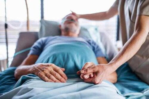 En sykepleier som tar seg av en sengeliggende mannlig pasient.