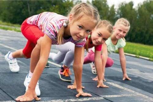 Tre unge jenter gjør seg klare til et løp.