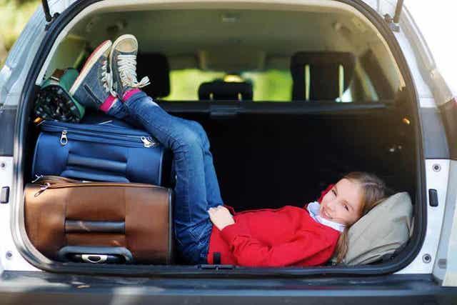 Et barn som hviler bak på en parkert bil med bena på koffertene