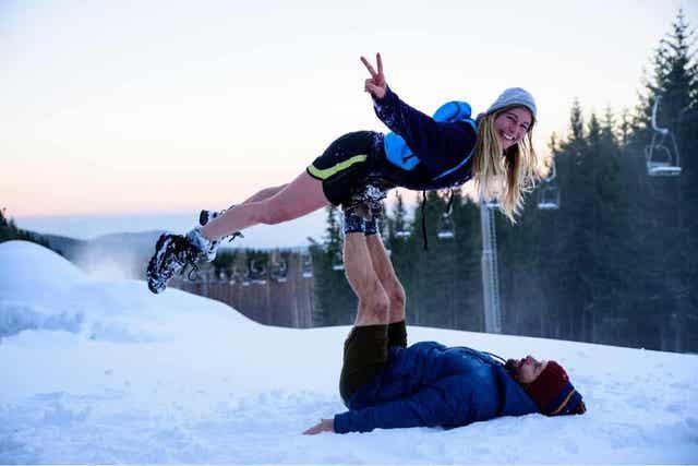 Et blåtonet bilde av en mann og en kvinne som leker i snøen på toppen av en skibakke, med stolheis i bakgrunnen