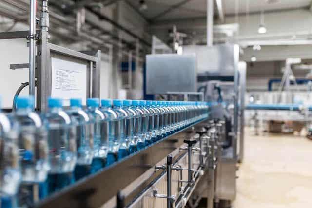 Vannflasker i plast som beveger seg nedover en fabrikklinje.