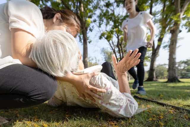 En besvimt kvinne i en park
