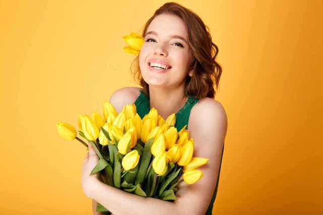 En kvinne som klemmer en bukett med gule tulipaner.