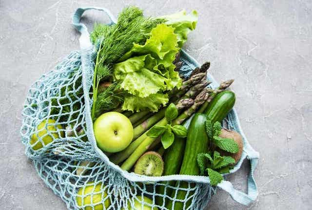 En pose full av grønne frukter og grønnsaker