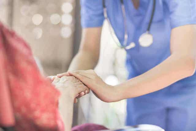 En sykepleier som holder hånden til en eldre kvinne i rullestol.