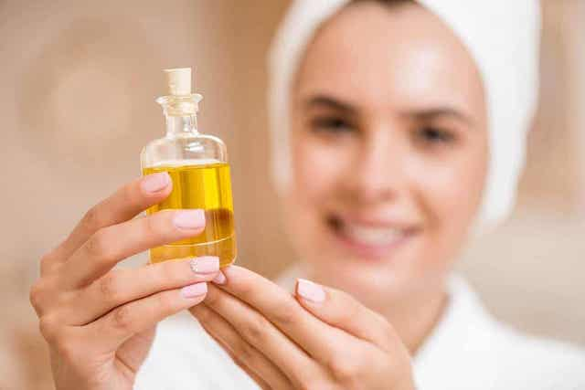 En kvinne som holder en flaske copaiba-olje.