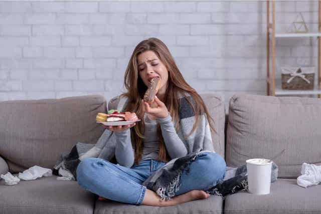 En kvinne som gråter og spiser