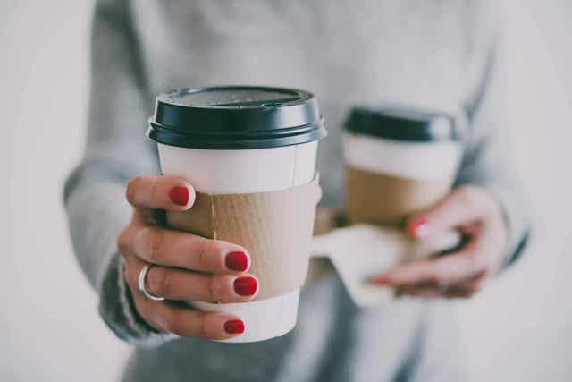 kvinne holder kaffe som kan motvirke tannbleking