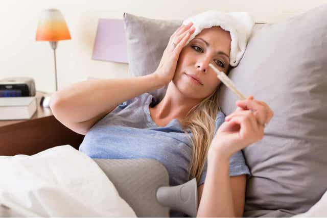 En kvinne som ligger i sengen med feber og tar temperaturen