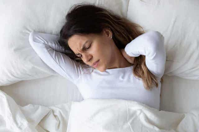 En kvinne som ligger i sengen og holder på nakken i smerter