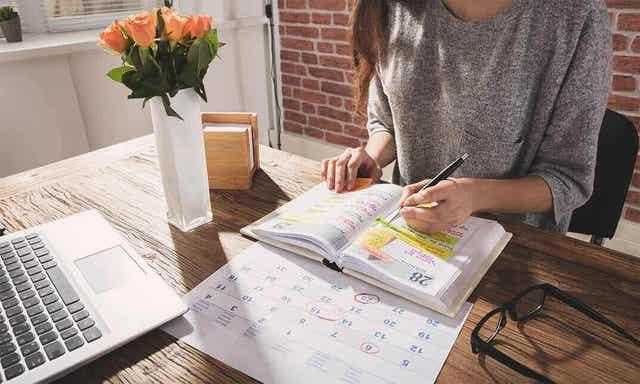 En kvinne som skriver i planleggeren.