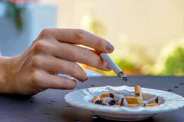 En person som holder en sigarett over og askebeger full av sneiper