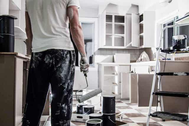 En mann som maler et hus