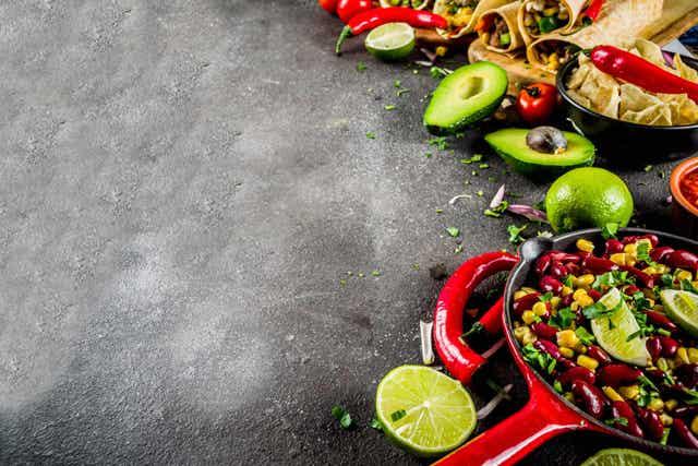 En stekepanne, bolle og skjærebrett, alt fullt av fersk meksikansk mat laget av bønner, frukter og grønnsaker