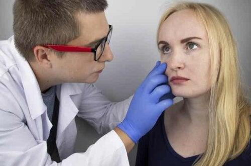 En lege som undersøker en kvinnes øyne