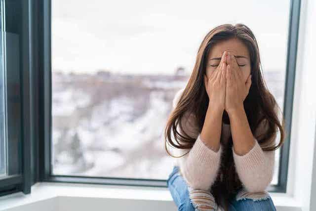 En kvinne som sitter og gråter ved et vindu.