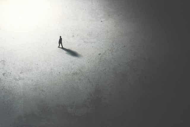 Silhuetten til en person som går fra mørke til lys