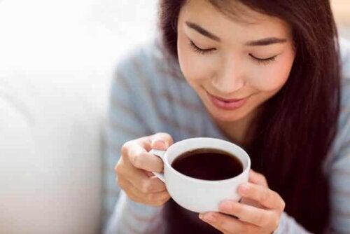 En kvinne som drikker en kopp kaffe.
