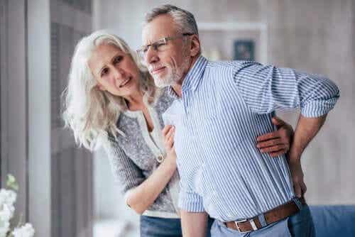 En kvinne som hjelper en eldre mann.
