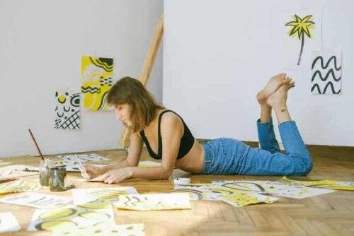 En kvinne som ligger på gulvet og maler alene.