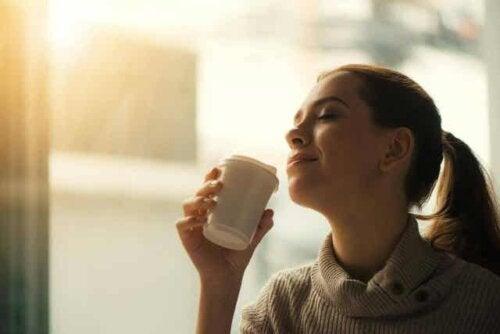 En kvinne som sitter på en kafé og drikker kaffe.